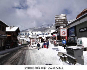 CHATEL, FRANCE - FEB 12, 2018 - Signpost and skiers  in small alpine village of Chatel, France