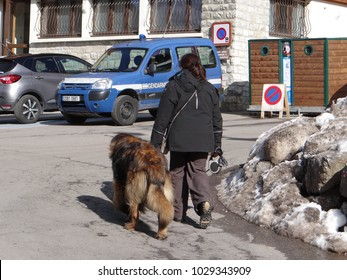CHATEL, FRANCE - FEB 20, 2018 - Police woman with her dog outside Gendarmerie in small alpine village of Chatel, France