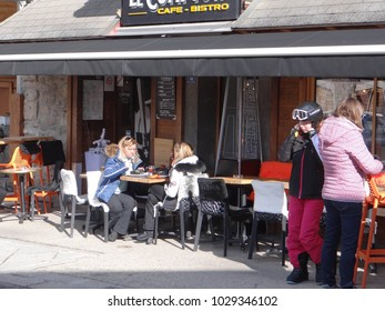 CHATEL, FRANCE - FEB 20, 2018 - Young women having lunch outdoors at a restaurant in small alpine village of Chatel, France