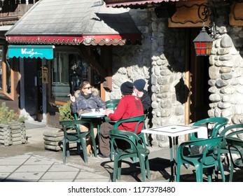 CHATEL, FRANCE - FEB 24 - Skiers relax in an outdoor bistro  in the windows  in Chatel, France