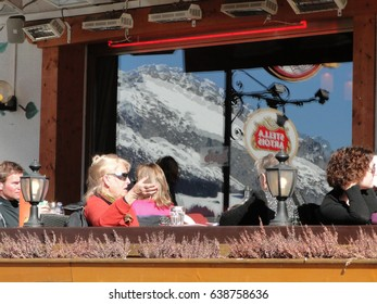 CHATEL, FRANCE - FEB 24 - Skiers relax in an outdoor bistro with the mountains reflected in the windows  on Feb 24, 2012 in Chatel, France