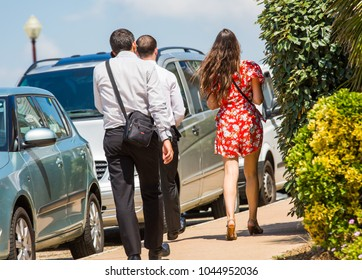 Chatelaillon, France - June 1, 2017: Rear view of two man dressed in a suit walking behind a very pretty brunette woman wearing a long red flower dress walking on pavement at Chatelaillon, France