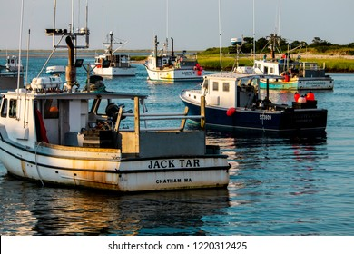 Chatham, Cape Cod, USA: July 20th, 2018: The Chatham fishing fleet is moored in the harbor as the sun begins to set for the day. Industrial fishing in New England is a demanding way to earn a living.