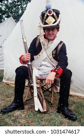 Chatham Kent England 2016. A renactor of the Napoleonic Wars wears the uniform of a French Fusilier sits with a Flintlock Musket in hand at a re-enactment event.