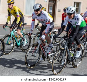 Chatillon-Coligny, France - March 10, 2019: Three cyclists (Andre Greipel, Lars Ytting Bak, Mike Teunissen) riding in the peloton, in Chatillon-Coligny during the stage 2 of Paris-Nice 2019.