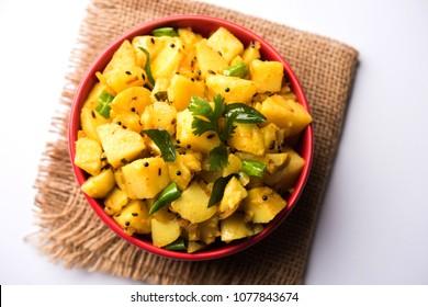 Chatpate Masala Aloo Sabzi fry OR Bombay potatoes served in a bowl, selective focus