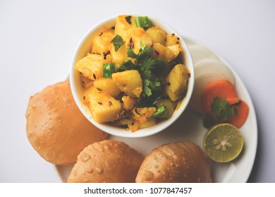 Chatpate Masala Aloo Sabzi fry OR Bombay potatoes served with fried puri or Indian bread made up of wheat in a plate, selective focus