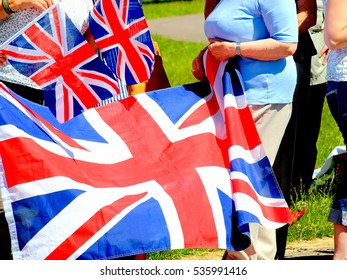 Chatsworth, Derbyshire, UK. July 10, 2014. Spectators with union flags waiting for the visit of the Queen at Chatsworth in Derbyshire.