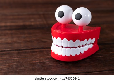 Chattering teeth toy with big eyes on a wooden background with copy space. Plastic red mouth with white fangs is a concept of oral hygiene and healthy teeth