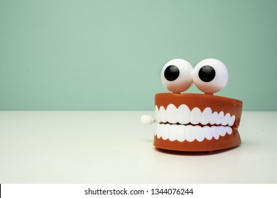 chattering teeth toy on a table with a green background. Jaw funny teeth