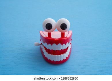 Chattering teeth toy wind up moving on blue background. Funny,comedy, relax time concept
