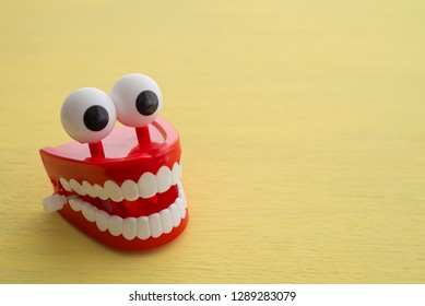 Chattering teeth toy wind up moving on yellow background. Funny,comedy, relax time concept