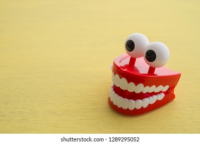 Chattering teeth toy wind up moving on yellow background. Funny,comedy, relax time or dental care concept