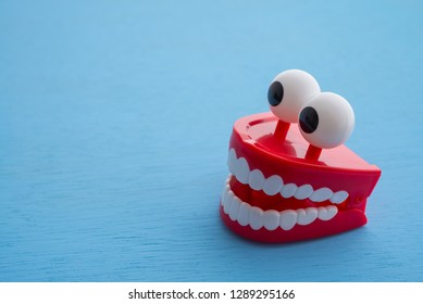 Chattering teeth toy wind up moving on blue background. Funny,comedy, relax time or dental care concept