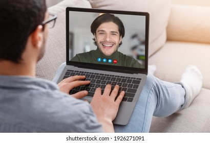 Chatting With Friend. Over the shoulder view of young man in glasses making online video call on laptop with smiling caucasian guy talking during virtual conference, sitting on the couch at home