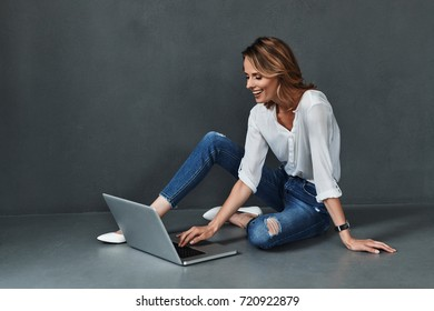 Chatting online. Attractive young woman in casual wear using computer and smiling while sitting on the floor against grey background