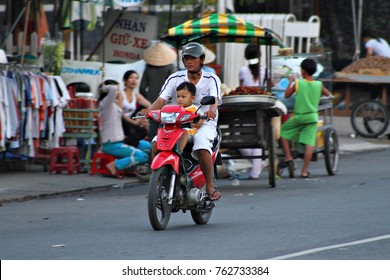 CHAU DOC, VIETNAM - 15 APRIL 2016: A man and child ride a scooter in Chau Doc. Bikes and scooters are regularly used as delivery vehicles in the busy streets of south east Asia. Editorial.