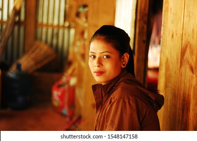 Chaubas / Nepal - October 2017: Beautiful villager teenage girl looking at camera with confidence. Slight smile on her pretty pure face. Sephia tones, wooden village house veranda. Blurry background.