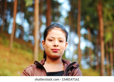 Chaubas / Nepal - October 2017: Beautiful villager teenage girl looking at camera with confidence. Slight smile on her pretty pure face. Woods on the bokeh background. Making sheep's eyes.