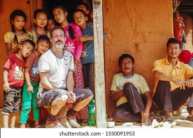 Chaubas / Nepal - October 2017: Curious Nepali villagers welcoming the new tourist, looking at camera. Colorful people. Nepalese hospitality. Relevance, interest from children on white man.