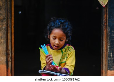 Chaubas / Nepal - October 2017: Female Nepalese school kid is playing with pencils in her hands. Sitting in front of the wooden door, happy, singing. Local, poor villager girl with yellow clothes.