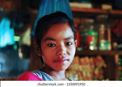 Chaubas / Nepal - October 2017: Head shot of beautiful 12 years old Nepalese girl in the small local market. Colorful scene, joyous facial expression.