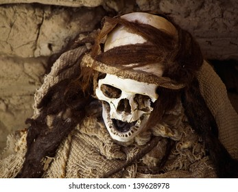Chauchilla mummy with white skull with remains of hair and clothes in the grave near Nazca, Peru