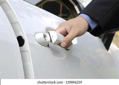 Chauffeur or driver hand opening white car door
