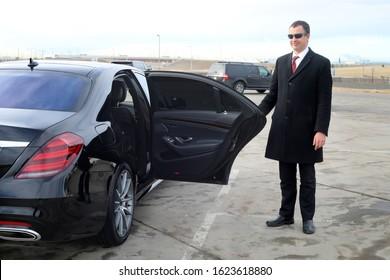 Chauffeur holds a rear passenger door open