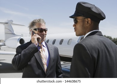 Chauffeur looking at senior businessman on call with private jet in the background