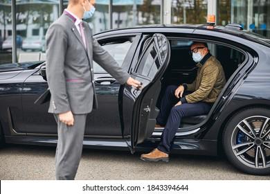 Chauffeur öffnet die Autotür für einen kaukasischen männlichen Passagier in einer Einwegmaske