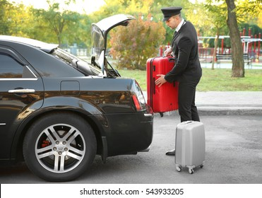 Chauffeur putting suitcase in car trunk