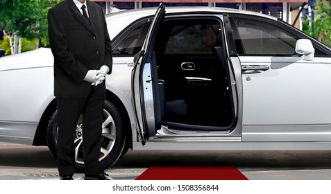 Chauffeur standing next to opened car door with red carpet