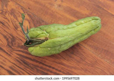 Chayote squash germinating on wooden background