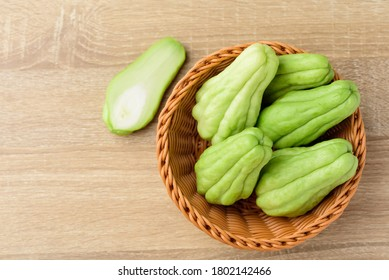Chayote squash or Mirlition squash in basket on wooden background,  organic vegetable, edible plant fruit