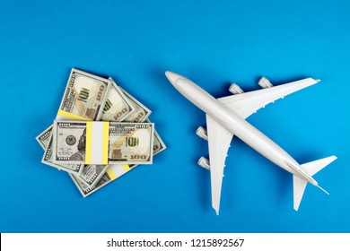 cheap flight tickets, low cost flights concept. toy airplane and money on a blue background