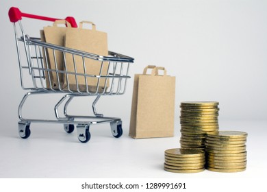 cheap and inexpensive shopping. shopping bags in grocery shopping trolley stacks of coins, white background
