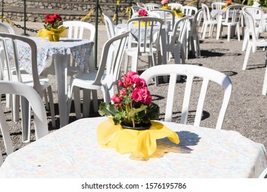 Cheap plastic chairs and tables outside with flowers