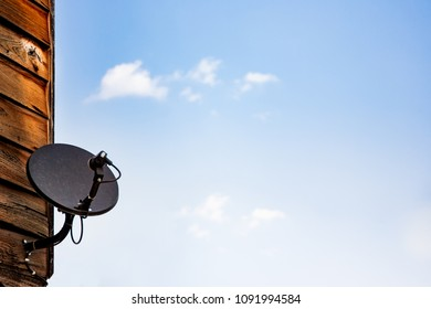 Cheap satellite dish mounted on wooden wall of old house with sky background.