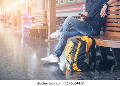 Cheap Travel and Lifestyle concept.Holiday Time,Young Traveler man wearing sneaker and sitting at train station.Asian Backpacker waiting train alone and plan trip in summer time with smart phone.