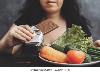 Cheat meal, diet breakdown, bad habits, sugar addiction, unhealthy eating, dieting and weight loss. Overweight woman eating chocolate refusing healthy food