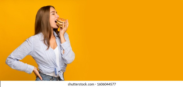 Cheat meal. Hungry millennial girl eating burger enjoying unhealthy fast food standing on yellow studio background. Panorama, empty space