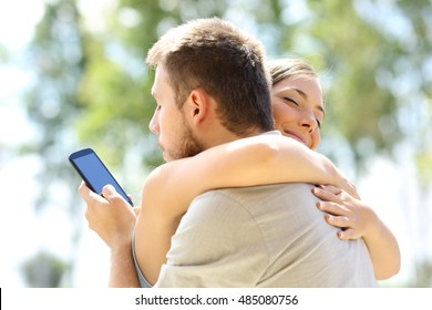Cheater texting with his other lover on phone and hugging his innocent girlfriend