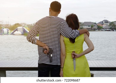 Cheating couple, a man put his arm around woman shoulder looking at the lake in the park. Boyfriend holding a gun girlfriend holding a knife in behind