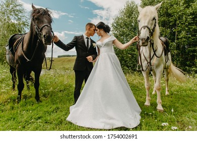 Cheboksary, Russia 11 july 2019: beautiful couple stands next to a horse. wedding day photo. bride and groom