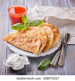 Cheburek - fried pie with meat and onions. Traditional dish of many turkic and mongolian peoples. Tomato juice.
