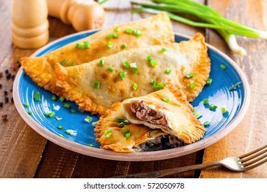 Chebureki on a plate. National Ukrainian, Russian, Turkish, Romanian and Tatar food. Meat pastry meal on a table.