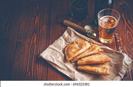 Chebureks with beer in rustic style on a wooden background. Pasties