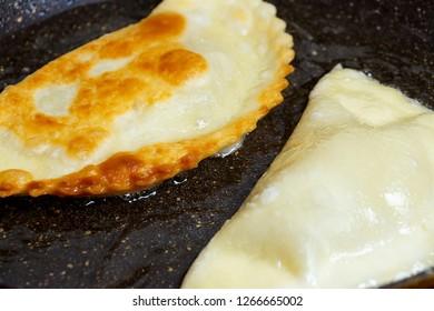 Chebureks are roasted on a hot skillet ruddy crispy tasty