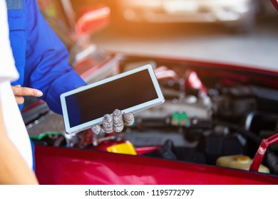 Check the condition of the car engine and oil / man hand holding  tablet